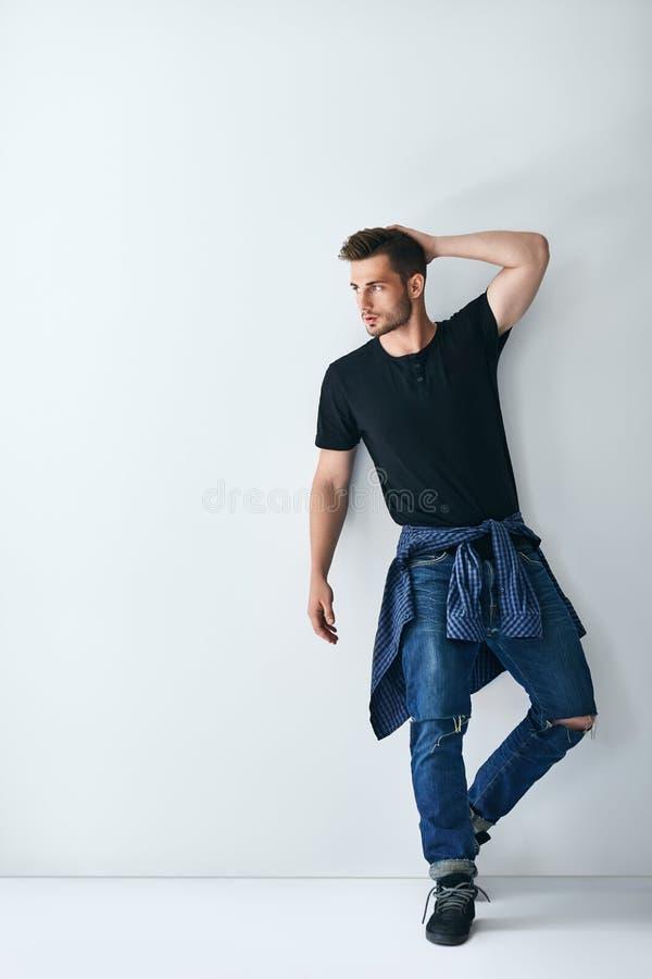 Retrato completo do comprimento do homem à moda considerável que inclina-se no wa branco fotos de stock