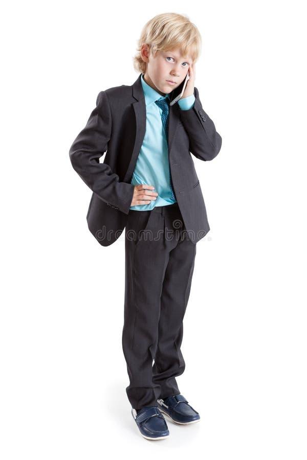 Retrato completo do comprimento do menino novo um fundo branco estando do homem de negócios com telefone celular à disposição imagens de stock