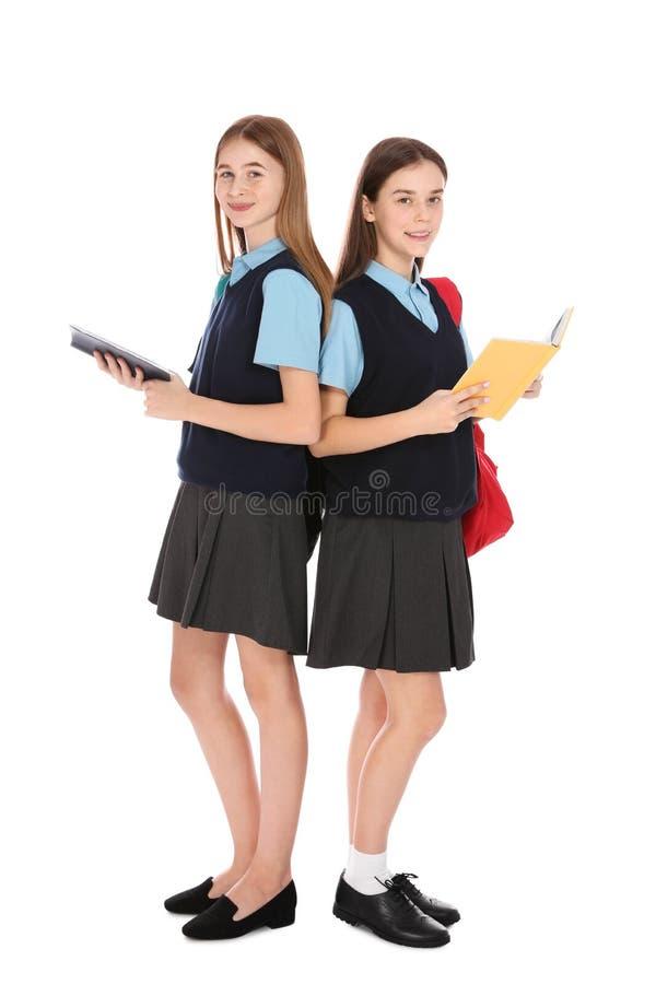 Retrato completo do comprimento dos adolescentes na farda da escola com os livros no branco foto de stock
