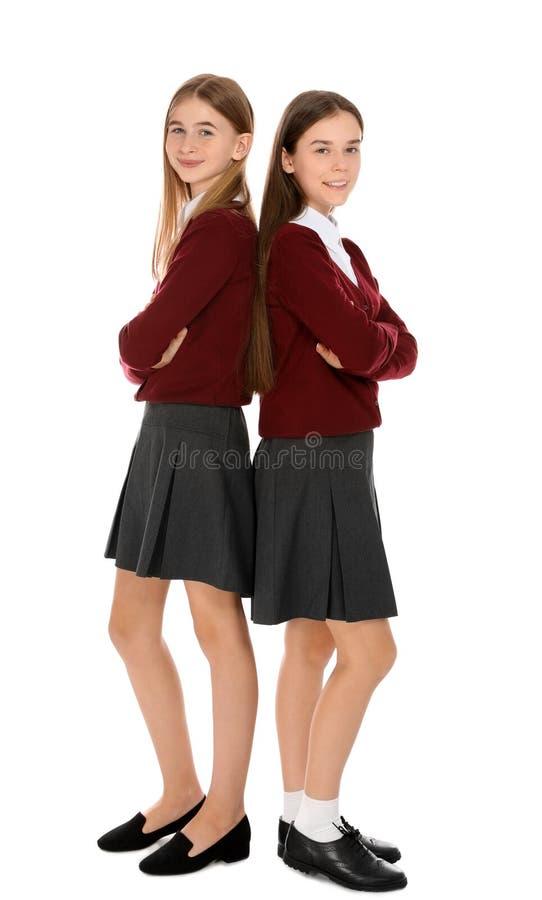 Retrato completo do comprimento dos adolescentes na farda da escola no branco fotos de stock royalty free
