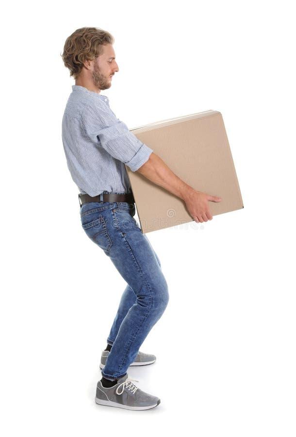 Retrato completo do comprimento do homem novo que leva a caixa de cartão pesada no fundo branco fotografia de stock royalty free