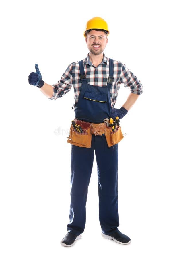Retrato completo do comprimento do trabalhador da construção profissional com a correia da ferramenta no branco fotografia de stock royalty free