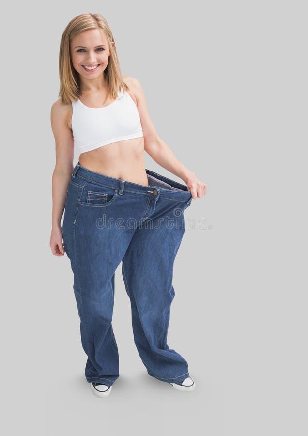 Retrato completo do corpo da mulher magro do ajuste que está e que veste sobre a roupa feita sob medida com fundo cinzento imagens de stock