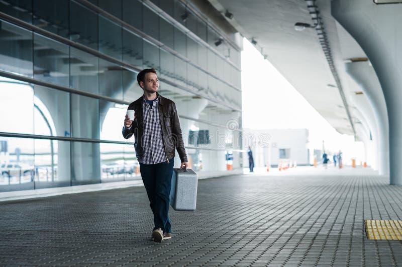 Retrato completo do corpo de um viajante masculino feliz que anda com sacos e café fotos de stock