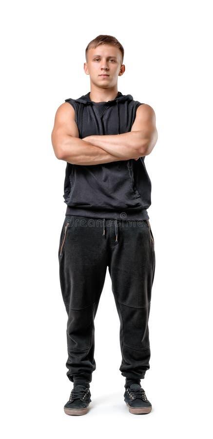 Retrato completo do corpo do homem novo muscled considerável com os braços dobrados isolados no fundo branco foto de stock royalty free