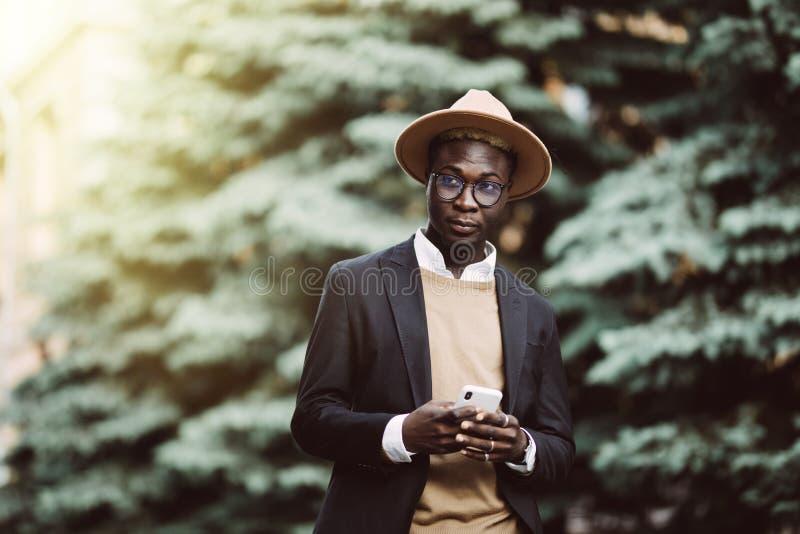 Retrato completo do corpo do homem de negócio africano novo que anda fora com telefone celular na rua imagens de stock royalty free