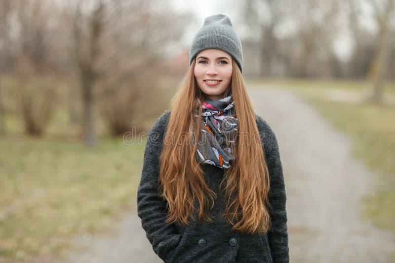 Retrato completo do estilo de vida do comprimento da mulher adulta nova e bonita com o cabelo longo lindo que levanta no parque d imagem de stock