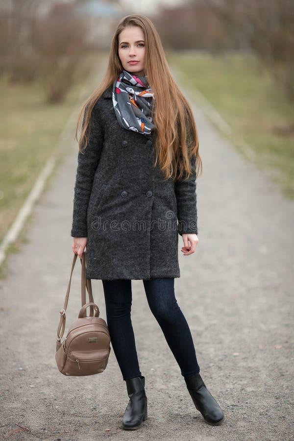 Retrato completo do estilo de vida do comprimento da mulher adulta nova e bonita com o cabelo longo lindo que levanta no parque d fotos de stock royalty free
