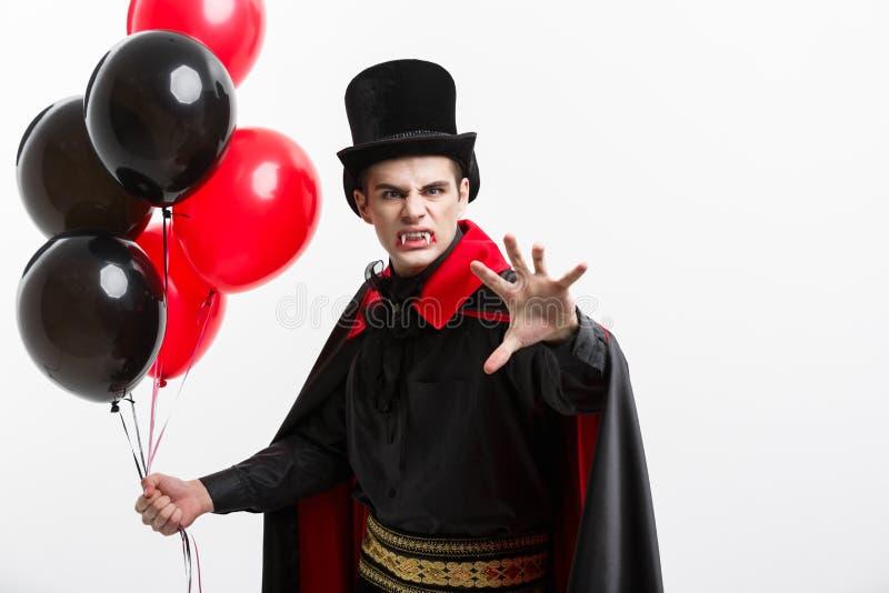 Retrato completo-lenght do vampiro caucasiano considerável no traje preto e vermelho do Dia das Bruxas imagens de stock royalty free