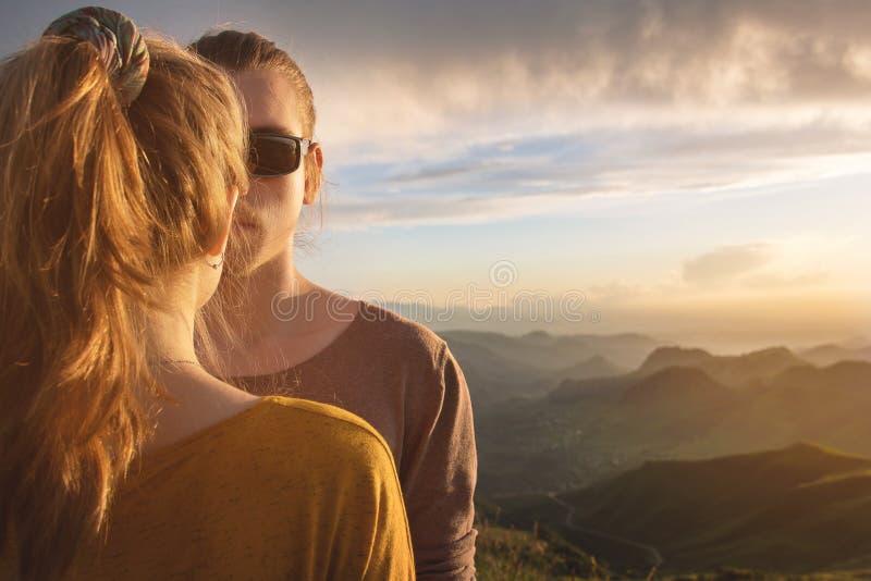 Retrato conceptual de um par novo no fundo de um céu do por do sol e de um vale bonito da montanha Metade do foto de stock