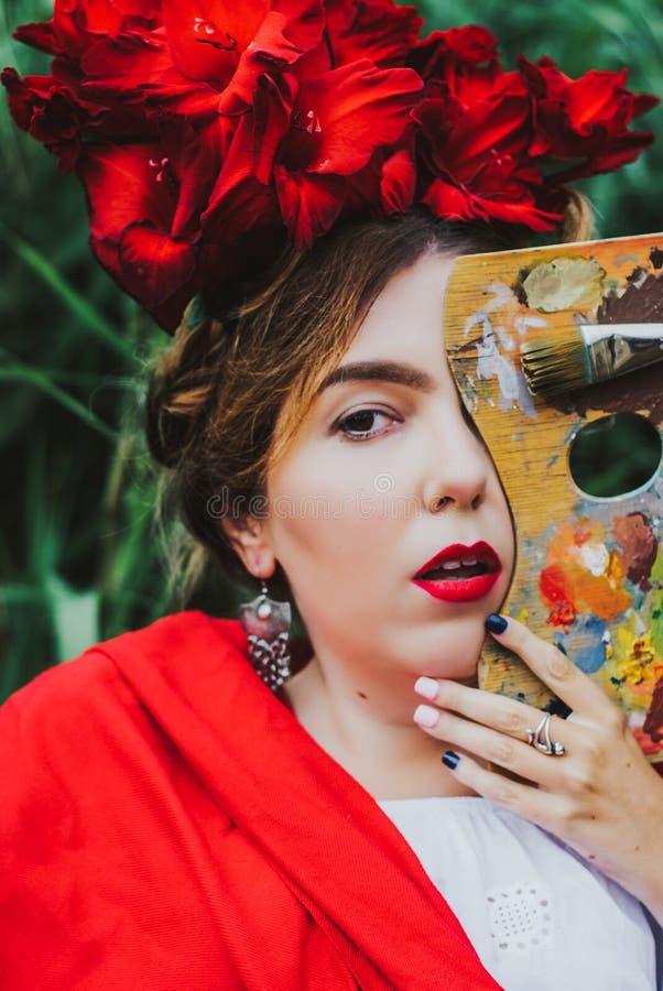 Retrato conceptual del artista hermoso de la mujer con los labios rojos, flores rojas en el pelo que mira de detrás de la paleta fotos de archivo libres de regalías