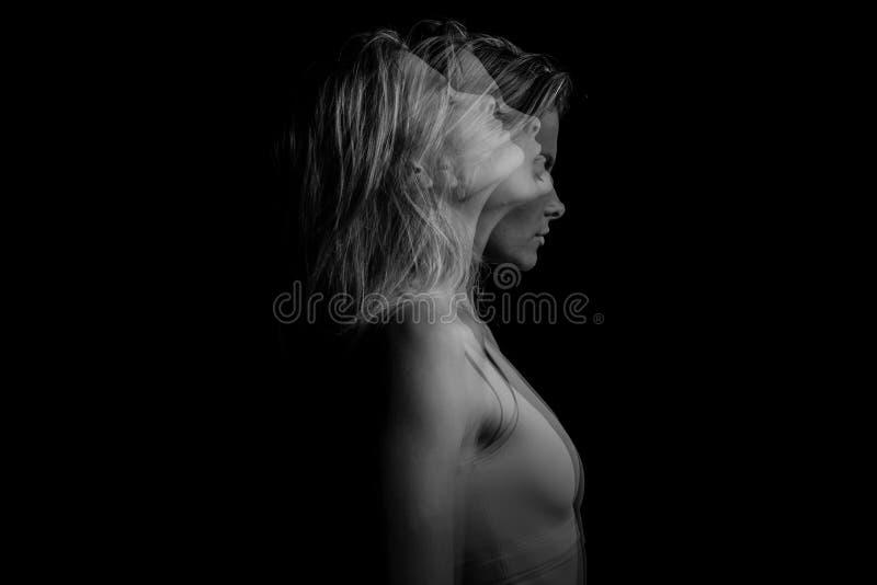 Retrato conceptual original ambiguo misterioso místico borroso hermoso del lado del perfil de la mujer rubia joven en un negro foto de archivo libre de regalías