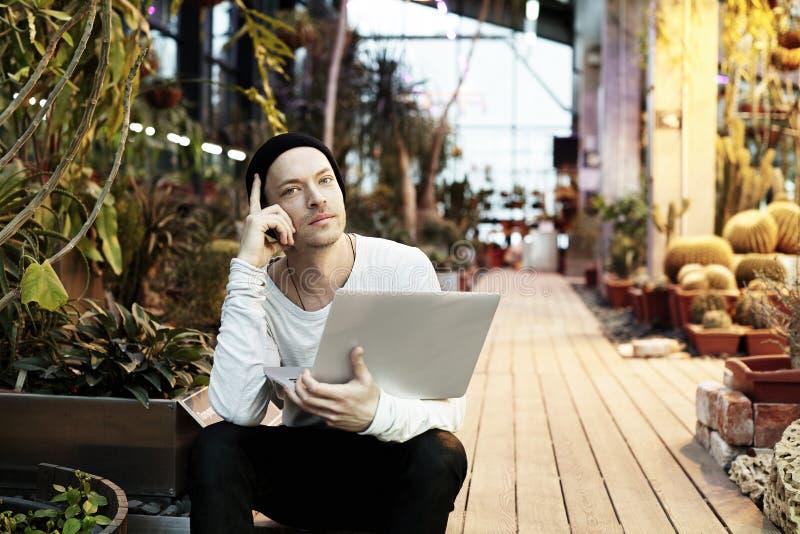Retrato considerável do homem do moderno que trabalha no laptop portátil Indivíduo no chapéu negro que sorri em um dia ensolarado foto de stock royalty free