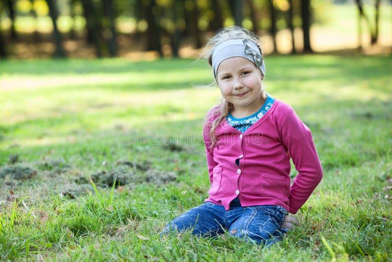 Retrato consideravelmente feliz da menina, sentando-se em genuflexões na grama, copyspace fotos de stock royalty free