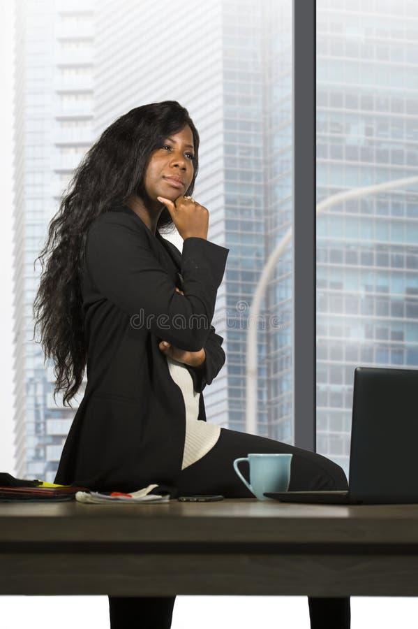 Retrato corporativo de la compañía de la empresaria afroamericana negra feliz y atractiva joven pensativa en la ventana de la ofi imagenes de archivo