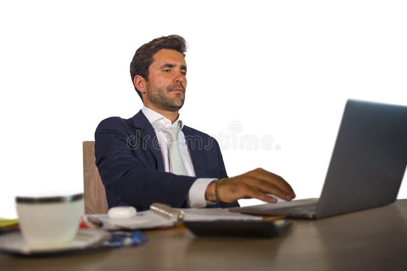 Retrato corporativo del hombre de negocios atractivo y eficiente joven que trabaja en el escritorio del ordenador portátil de la  foto de archivo