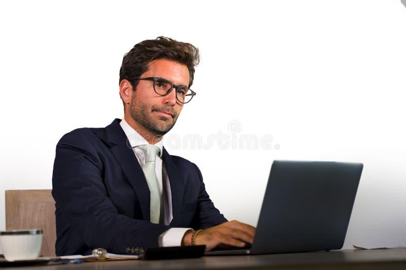 Retrato corporativo del hombre de negocios atractivo y eficiente joven que trabaja en el escritorio del ordenador portátil de la  imágenes de archivo libres de regalías