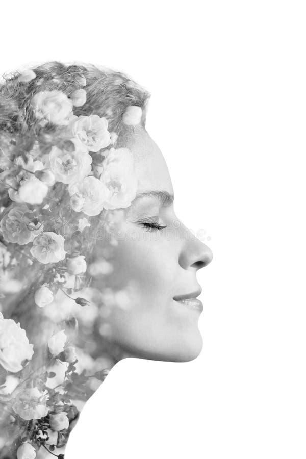 Retrato criativo da jovem mulher bonita feito do efeito da exposição dobro usando a foto de flores das rosas, isolada no backgr b imagem de stock