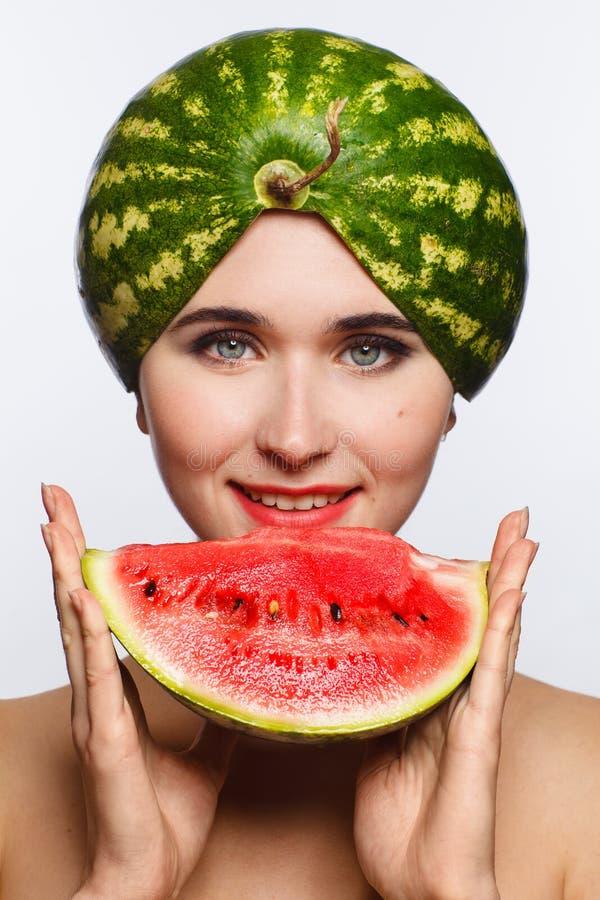Retrato criativo de uma mulher com uma melancia em sua cabeça e em suas mãos Fundo branco foto de stock royalty free
