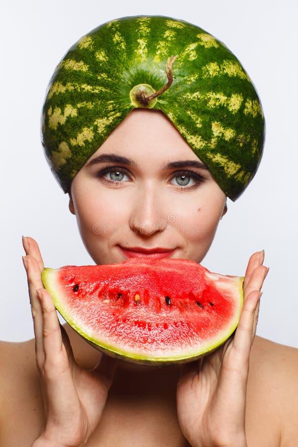 Retrato criativo de uma mulher com uma melancia em sua cabeça e em suas mãos Fundo branco imagens de stock