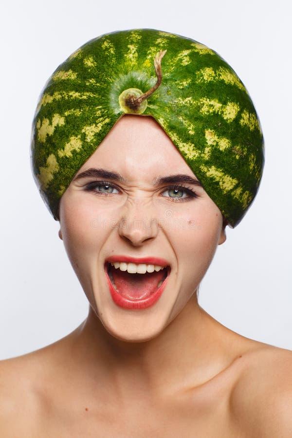 Retrato criativo de uma mulher com uma melancia em sua cabeça em vez de um chapéu Fundo branco fotos de stock royalty free