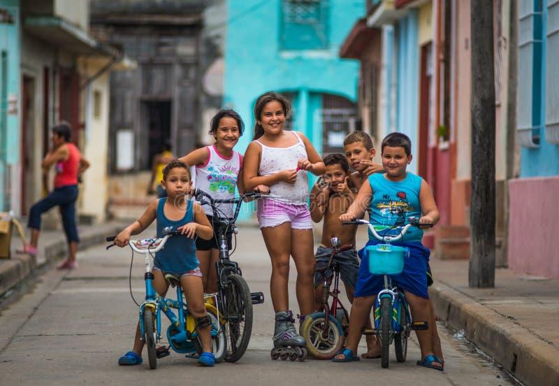 Retrato cubano feliz das crianças na aleia colonial colorida pobre da rua com cara do sorriso, na cidade velha, Cuba, América foto de stock