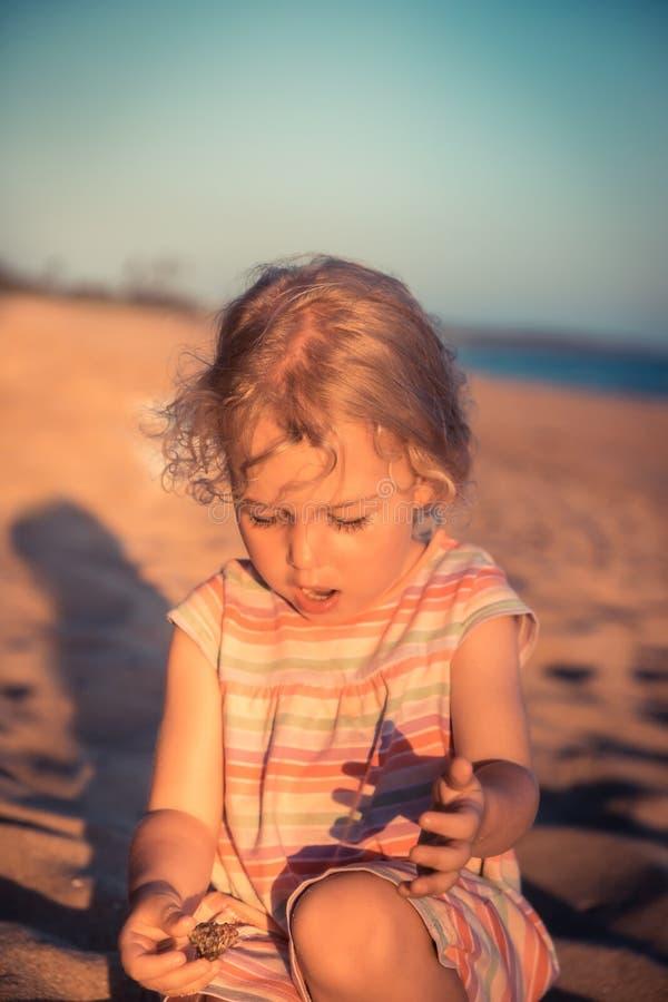 Retrato curioso del ni?o de la muchacha del ni?o que juega en la playa con el cangrejo de ermita?o durante forma de vida de la ni imagen de archivo libre de regalías