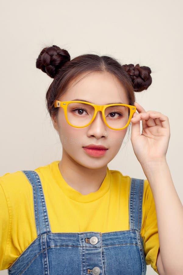 Retrato da Ásia segurando seus óculos com dois pães de cabelo, usando um bungaree de jeans imagem de stock