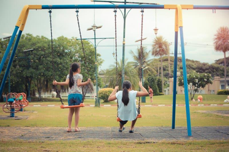 Retrato da ação das crianças que têm o divertimento que balança no parque fotos de stock royalty free