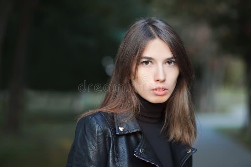 Retrato da arte de uma mulher moreno bonita nova que levanta fora no fundo obscuro do parque de couro preto da cidade do againt d foto de stock