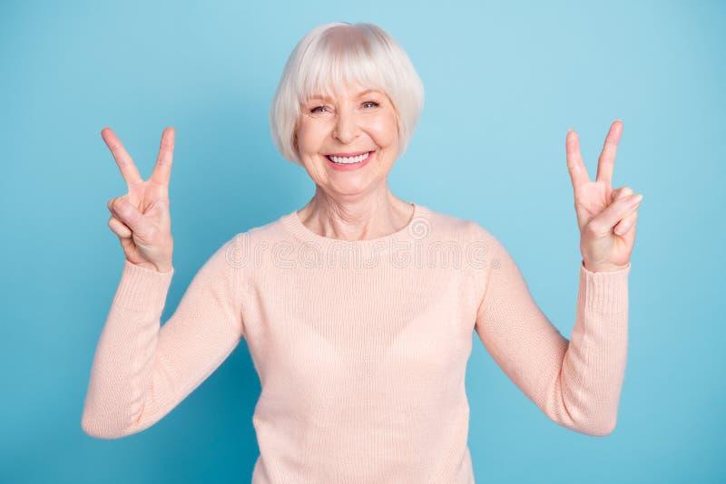Retrato da avó encantador com o v-sinal de fatura de sorriso toothy que veste a ligação em ponte pastel isolada sobre o fundo azu fotografia de stock