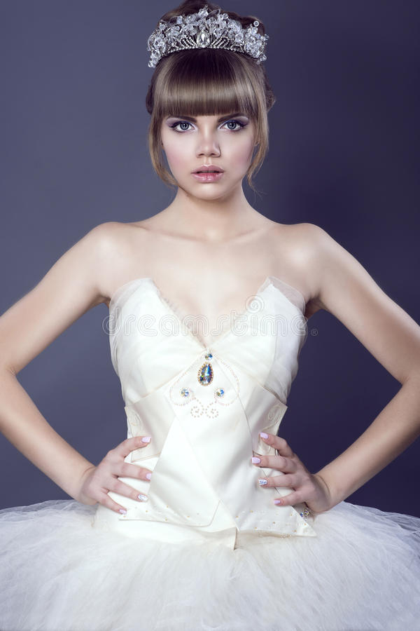 Retrato da bailarina bonita nova no espartilho branco vestindo e no tutu da coroa de cristal da joia que estão com suas mãos nos  fotografia de stock