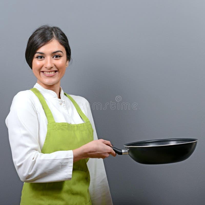 Retrato da bandeja bonita da terra arrendada do cozinheiro chefe da mulher contra o fundo cinzento imagem de stock