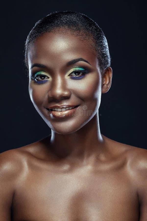 Retrato da beleza da menina africana étnica considerável de sorriso, na obscuridade imagem de stock royalty free
