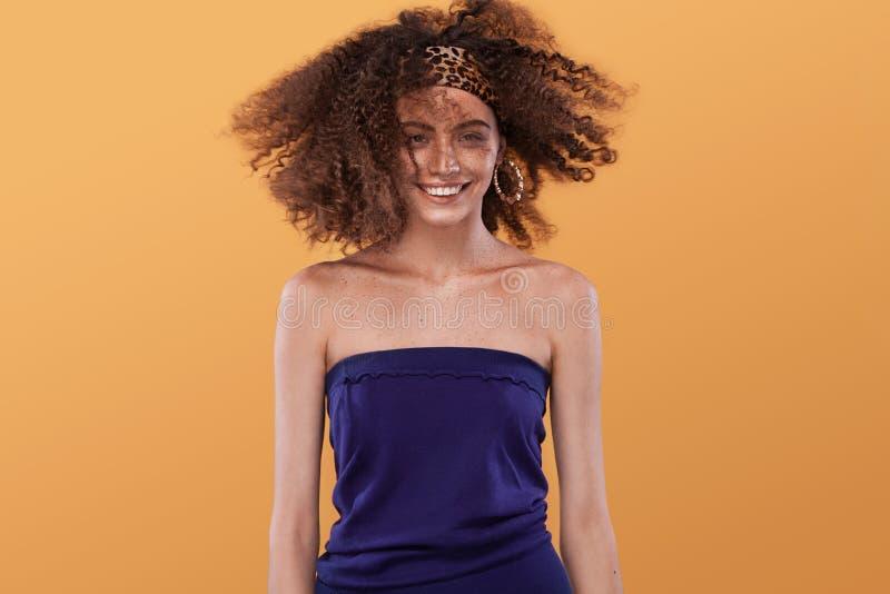 Retrato da beleza da menina com penteado afro Menina que levanta no fundo amarelo, olhando a câmera, sorrindo Tiro do estúdio foto de stock