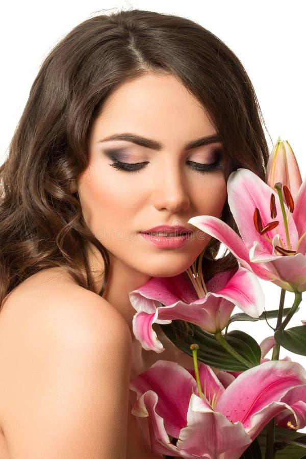 Retrato da beleza da mulher moreno nova perto do lírio cor-de-rosa foto de stock royalty free