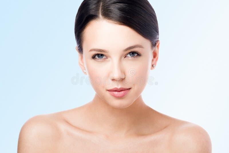Retrato da beleza de uma mulher bonita nova com um sorriso claro Makeu do Nude Isolado no azul foto de stock