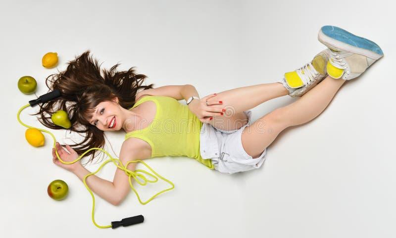 Retrato da beleza de uma mulher cercada por frutos e de uma corda de salto que encontra-se no assoalho fotografia de stock
