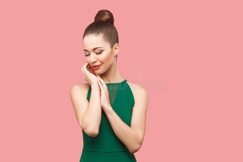 Retrato da beleza da jovem mulher bonita feliz com penteado e composição do bolo na posição verde do vestido com olhos fechados,  imagem de stock royalty free