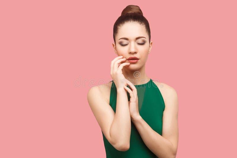 Retrato da beleza da jovem mulher bonita séria calma com penteado e composição do bolo na posição verde do vestido, com fechado s foto de stock royalty free