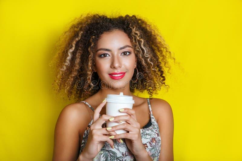 Retrato da beleza da menina afro-americano nova com penteado afro Menina que levanta no fundo amarelo, olhando a câmera fotos de stock