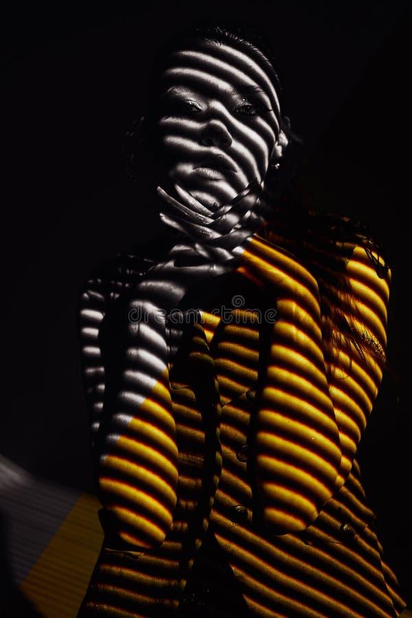 Retrato da beleza da menina com listras e sombras claras na cor do ouro Foto do retoque da qualidade da altura Encanto da forma foto de stock royalty free