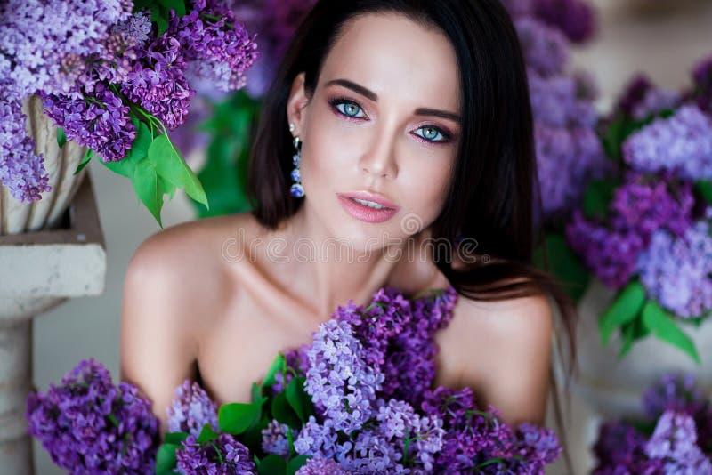 Retrato da beleza Mulher bonita com os bordos sensuais que sentam-se entre as flores violetas Cosméticos, composição perfumery imagens de stock royalty free