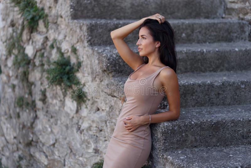 Retrato da beleza no perfil de uma menina moreno quente, 'sexy', levantando perto das escadas velhas feitas da pedra, nas horas d imagens de stock