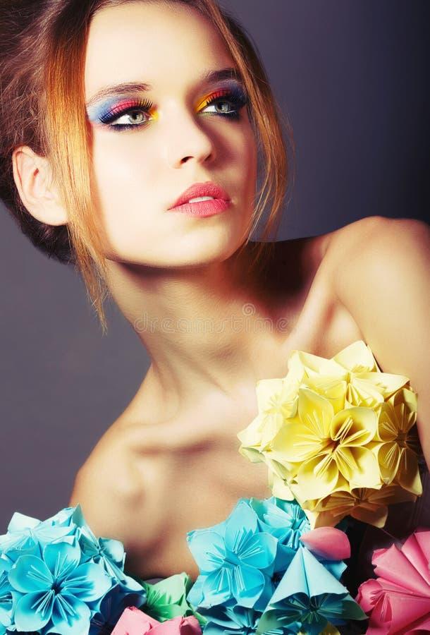 Retrato da beleza nova com as flores coloridas do origâmi. Composição brilhante do olho foto de stock