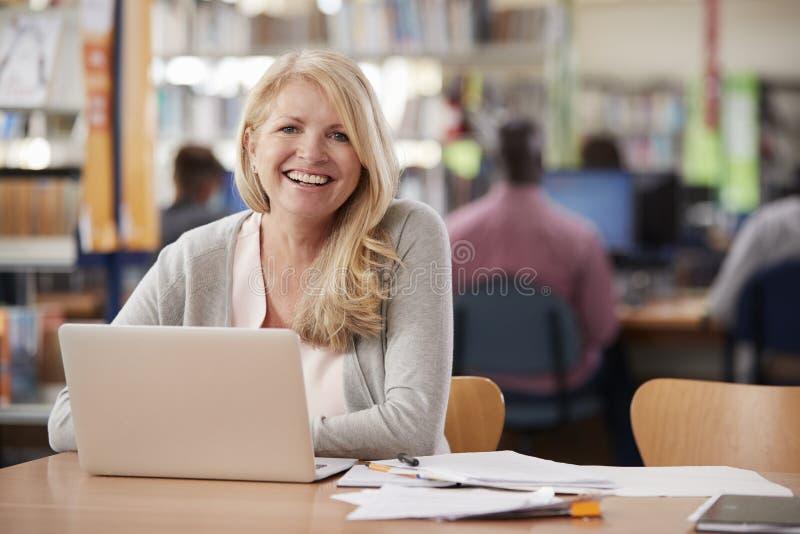 Retrato da biblioteca madura de Using Laptop In do estudante fêmea imagem de stock royalty free