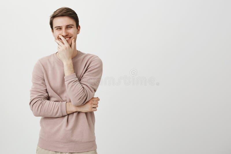 Retrato da boca masculina europeia encantador positiva da coberta com mão ao rir e ao olhar de lado, estando sobre imagens de stock