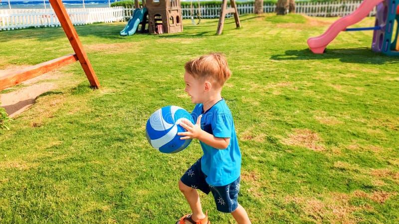 Retrato da bola de sorriso feliz da terra arrendada do rapaz pequeno nas m?os e no corredor na grama no campo de jogos das crian? imagens de stock royalty free