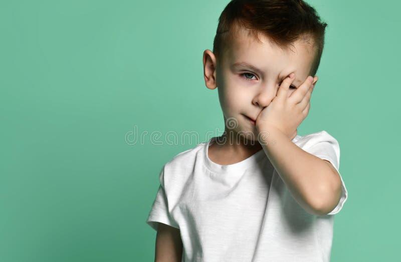 Retrato da cabeça de inclinação furada triste infeliz do menino da criança na palma que olha com virada fotos de stock royalty free