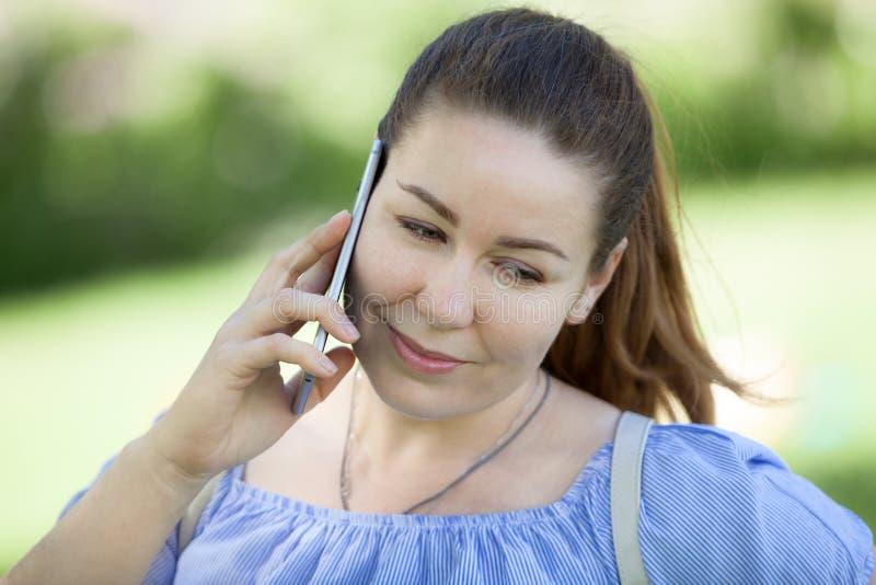 Retrato da cabeça e da cara da mulher europeia bonita que fala pelo telefone celular na natureza imagens de stock